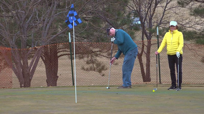 A pair of golfers line up their putts on an unusually warm day at the Arrowhead Country Club...