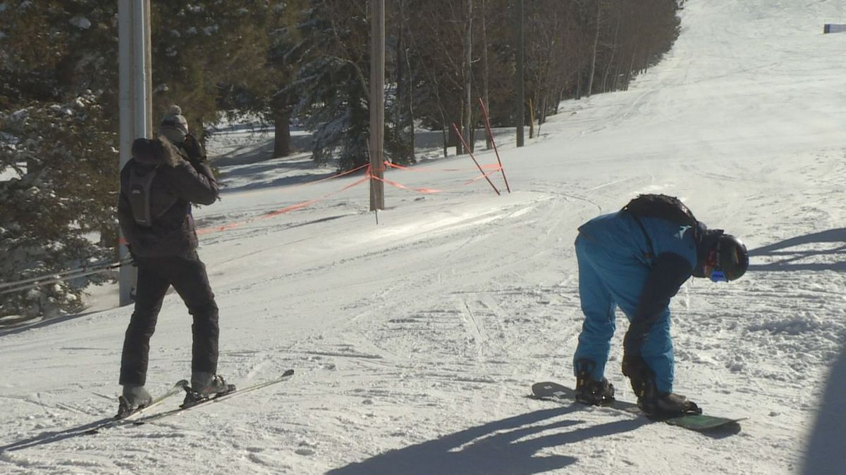 Skier and snowboarder prepare to hit the slopes at Terry Peak.