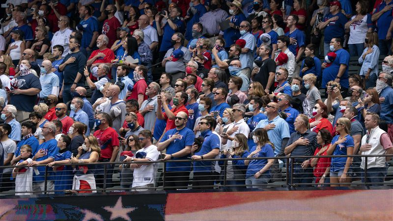 Fans stand for the national anthem before a baseball game between the Texas Rangers and the...