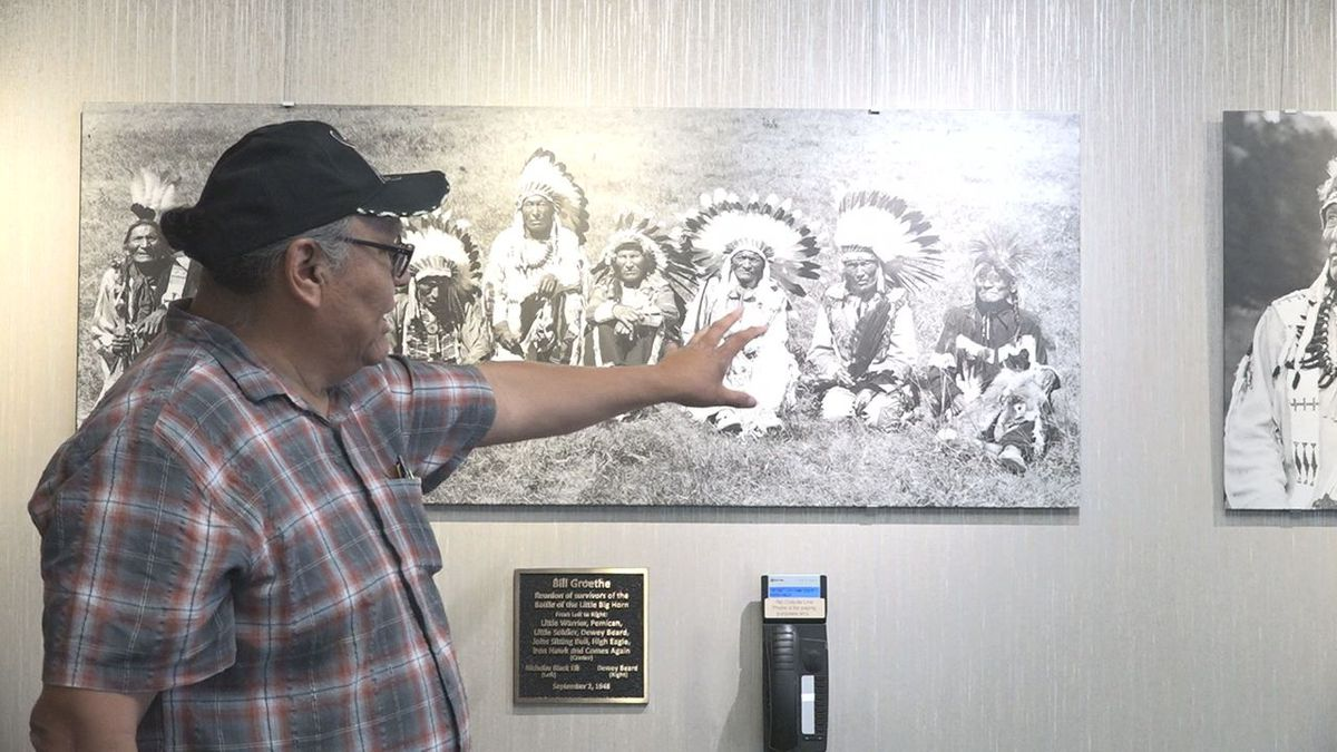 A descendant of the Wounded Knee Massacre points out family member on a display at Rapid City Regional Airport. (KOTA TV)