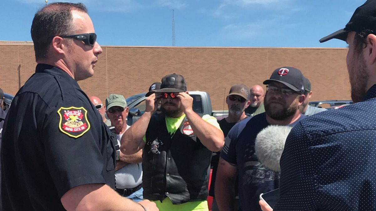 Lt. Andy Becker of the Rapid City Police Department talks with a group of people who claim...