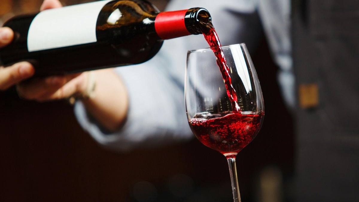 Waiter pouring red wine into wineglass. Sommelier or bartender pours alcoholic drink without...