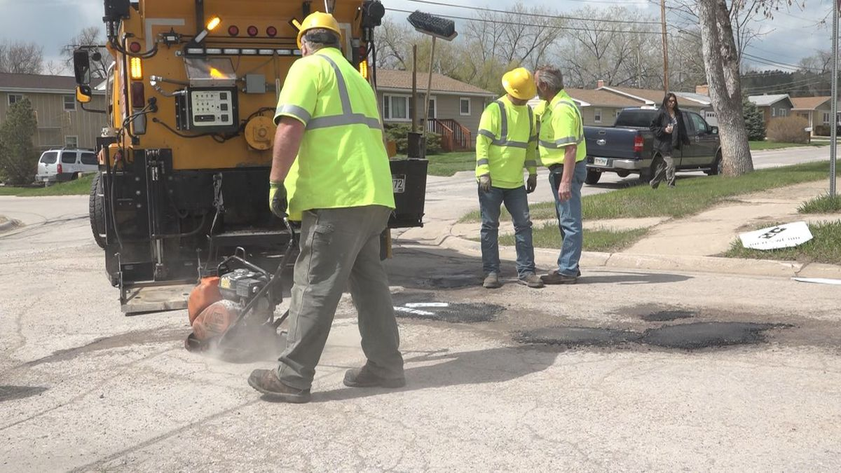 Pothole repair on West St Patrick Street. Street Department Superintendent Dale Pfeifle spray paints  Domino's logo once the hole is filled.