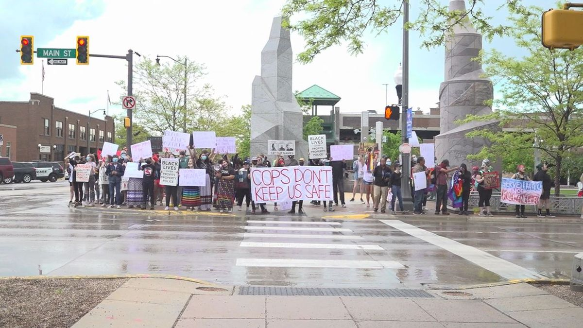 Two small group of protesters come together in harmony on Main Street Wednesday afternoon in Rapid City.