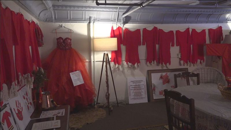 Dresses on walls with names of loved ones lost.
