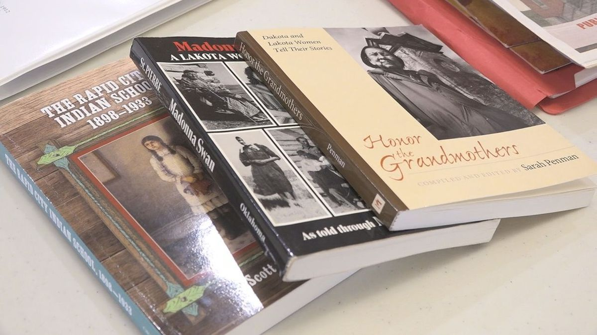 A volunteer of the Rapid City Indian Boarding School Research team brings books to the meeting...