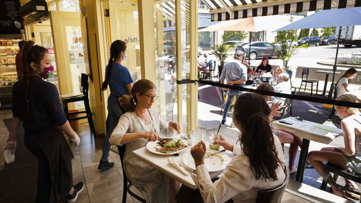 Liz Cahn, center, and her daughter Cara eat lunch at Meli-Melo Creperie, Juice Bar & Cafe, Wednesday, June 17, 2020 in Greenwich, Conn. The state began Phase 2 Wednesday, which includes allowing indoor seating at restaurants during the coronavirus pandemic. (AP Photo/Mark Lennihan)