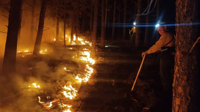 Firefighters hold the line against a wild land fire that started in rough terrain north of...