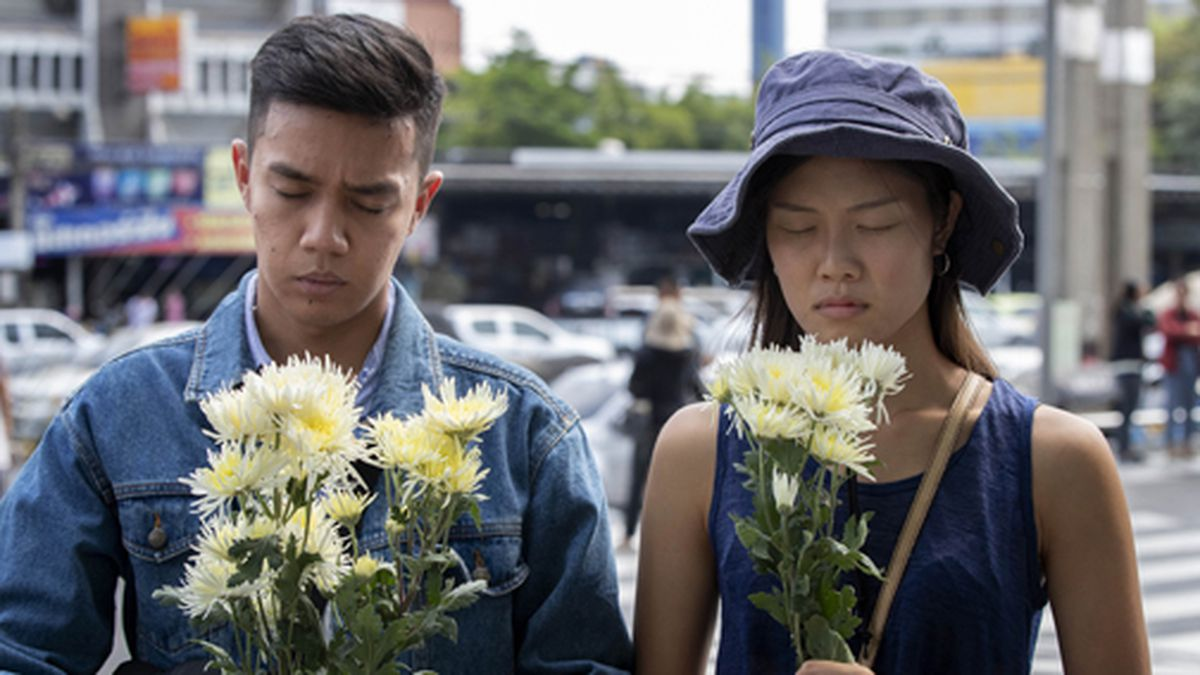 A couple offers flowers at the scene of a deadly mass shooting outside the Terminal 21 shopping mall on Monday, Feb. 10, 2020, in Korat, Nakhon Ratchasima, Thailand. (AP Photo/Gemunu Amarasinghe)
