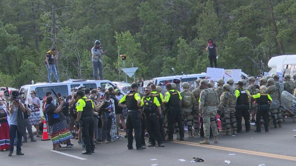 Protesters standing on white vans look down on a crowd of fellow demonstrators while under the observation of Pennington County Sheriff's deputies and National Guardsmen. Protest organizers blocked the road leading to Mount Rushmore with the vehicles - two of which had their tires removed to make them difficult to move out of the road.