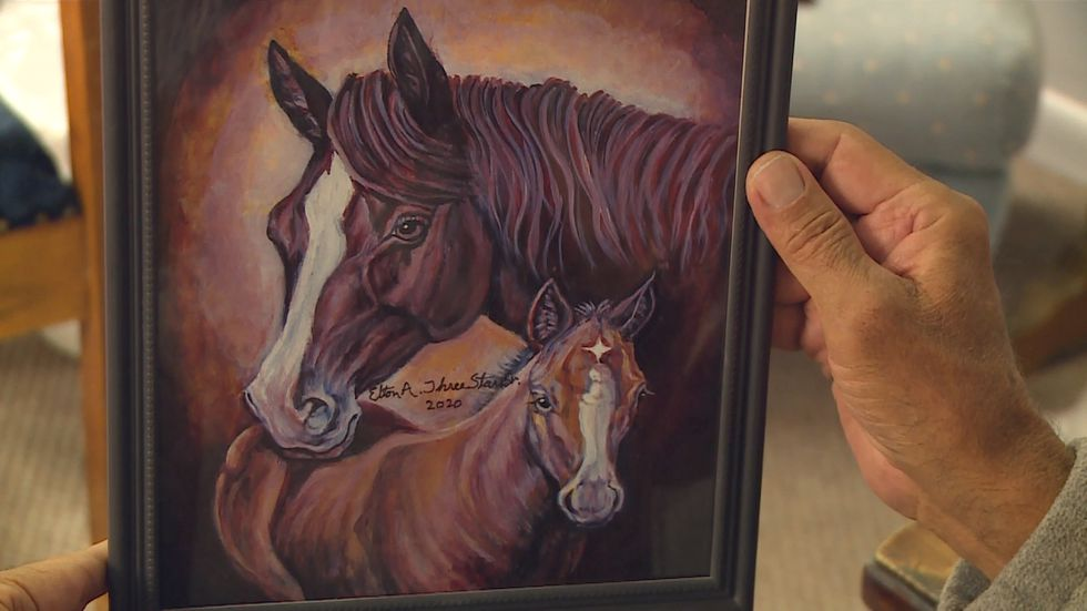 Martin native Elton Three Stars holds up one of his latest paintings depicting a dam and her...