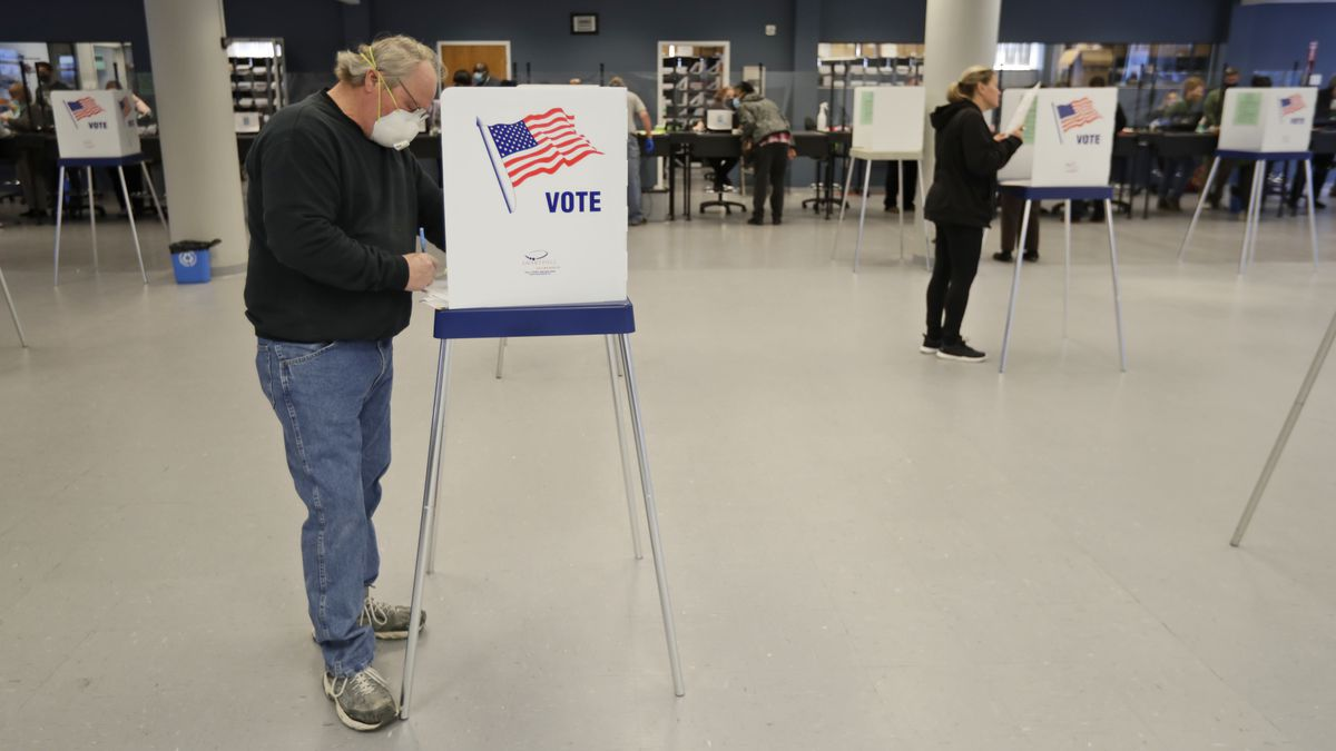 This Tuesday, April 28, 2020 file photo shows Jerome Fedor, left, voting using social distancing at the Cuyahoga County Board of Elections, in Cleveland, Ohio.