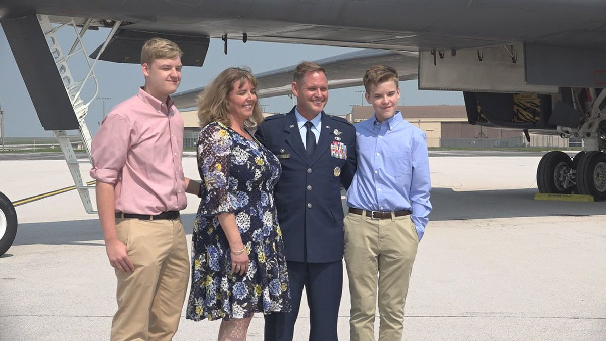 Colonel David Doss happily stands with his family after he is sworn in as the new 28th Bomb...