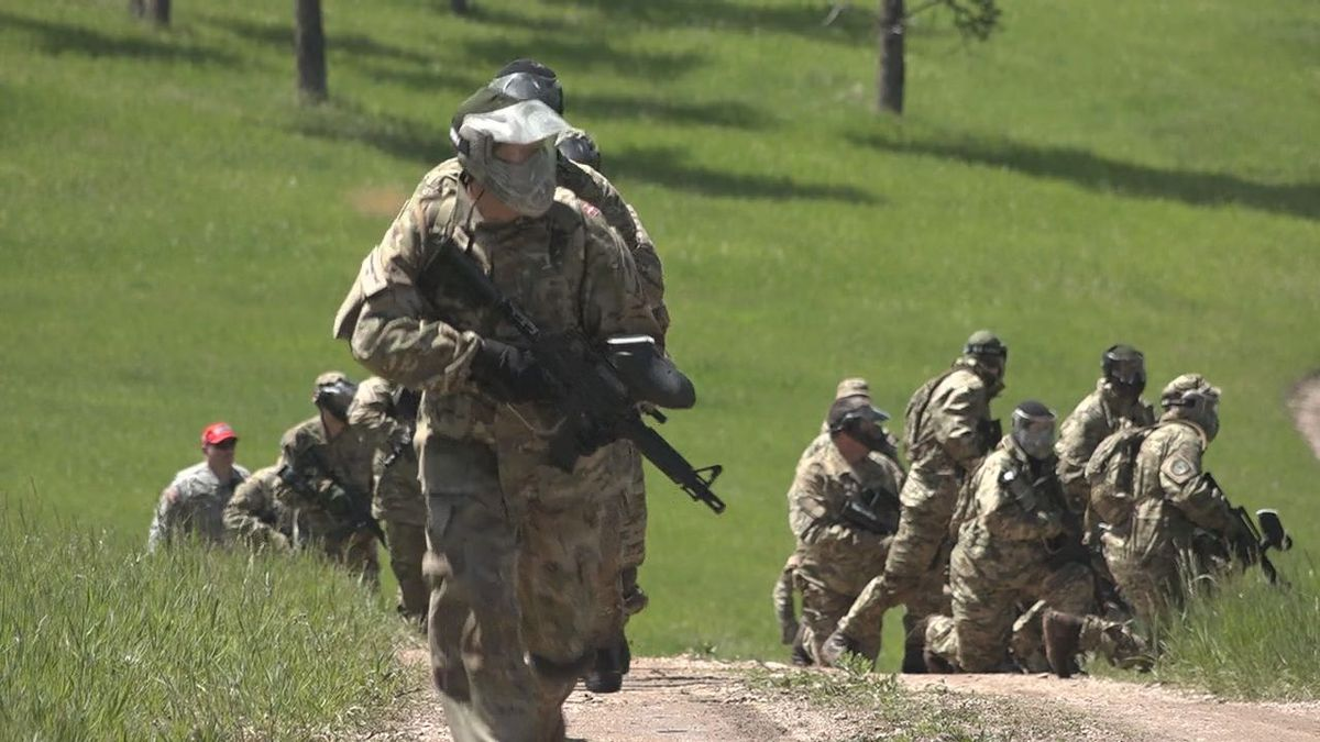 Danish National Guard soldiers run in West Camp Rapid for Golden Coyote paintball exercise. (KOTA TV)
