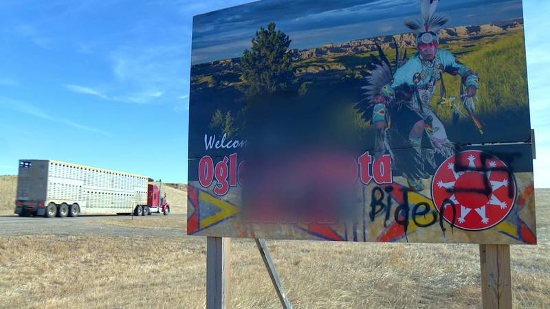 A semi-truck passes by a vandalized sign meant to welcome drivers entering Pine Ridge Indian...