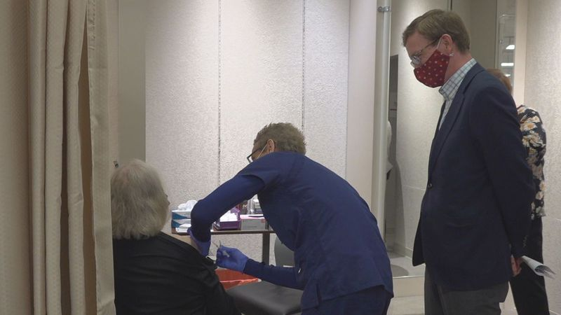 Rep. Dusty Johnson (R- S.D.) watches Joan Petersen get vaccinated at Monument Health's...