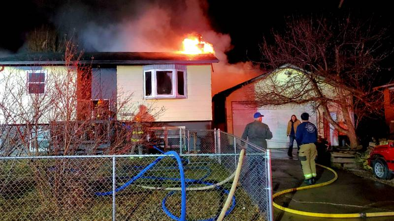 Fire officials talk as firefighters prepare to enter an Ennen Drive residence in Rapid Valley,...
