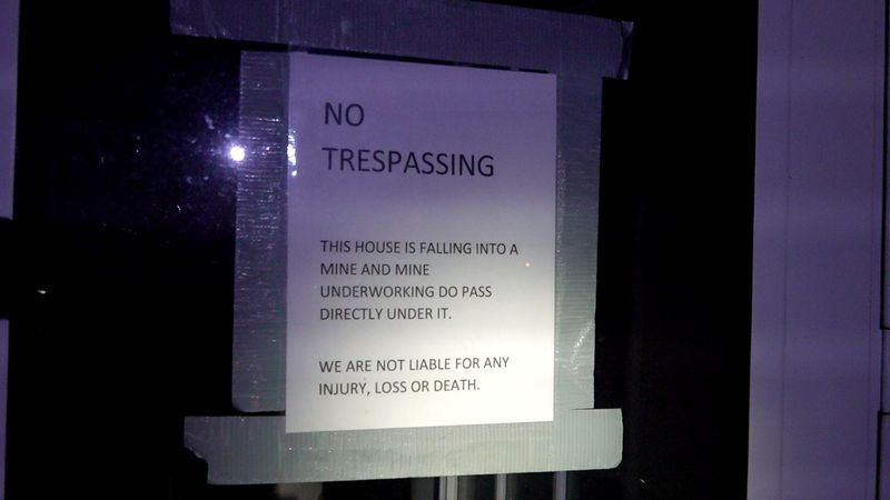 "A sheet of paper taped to a window reading ""NO TRESPASSING"" warns the reader from entering one..."