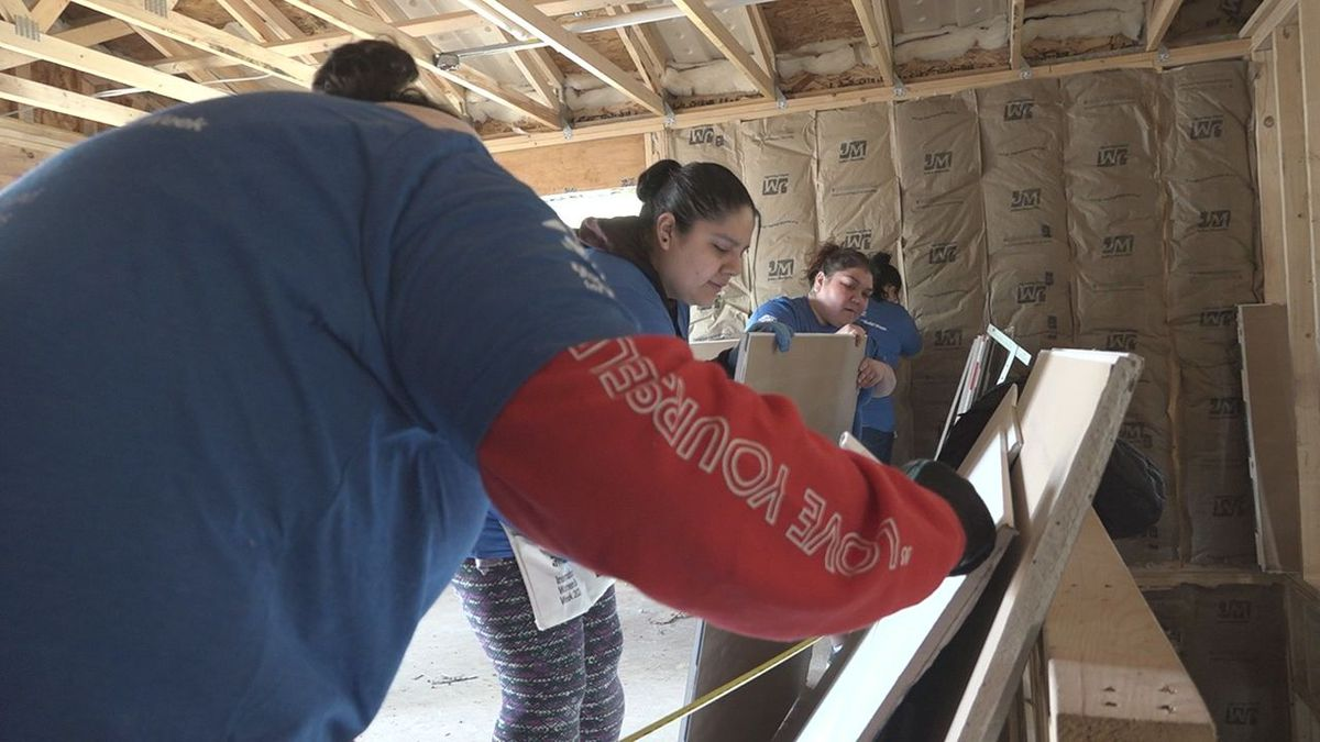 A group of women measure and cut boards to help build a home in Rapid City. (KOTA TV)